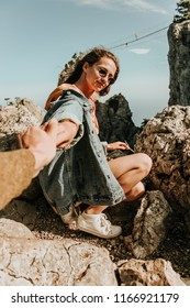 Camping outdoors and Mountains. Young woman wits backpack is enjoying the view. Blue sea or Atlantic Ocean in Europe. Film Vintage Modern colors. adventure at the weekend.