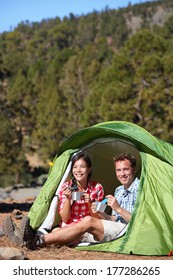 Camping people - couple eating food in tent smiling happy outdoors in forest. Happy multiracial couple having fun relaxing after outdoor activity hiking. Asian woman, Caucasian man.