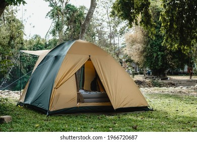 Camping picnic green tent campground in outdoor hiking forest.  Camper while campsite in nature background at summer trip camp. Adventure Travel Vacation concept