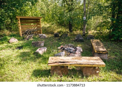 Camping place with fireplace and benches in the forest