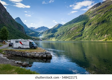 Camping site at Geiranger fjord shore. Evening light and calm summer day in Norway.