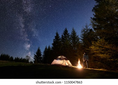 Camping site in mountain valley. Young man standing in front of tourist tent at burning bonfire under dark blue starry sky on pine trees background. Beauty of nature, tourism and traveling concept.