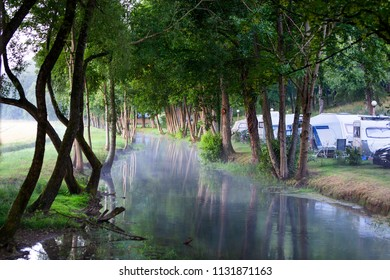Camping site near foggy water in the early morning in Louvemont in France