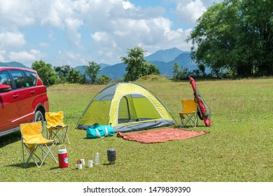 Camping site on grass field with tent and car beside tent. Leisure activity