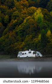 Camping site on a lake with caravans in the background nice autumn trees. Family vacation travel, holiday trip in motorhome, Caravan car Vacation. Misty morning.