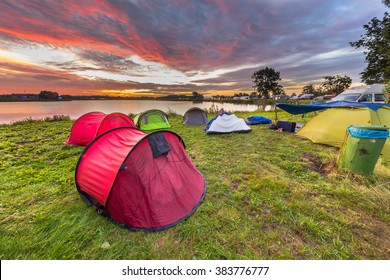 Camping spot with dome tents near lake on a music festival camp site under beautiful sunrise