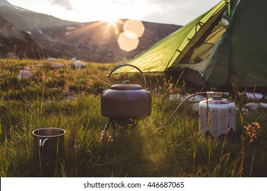 Camping teapot and cap on the grass at sunrise time. Mountains of Bulgaria.