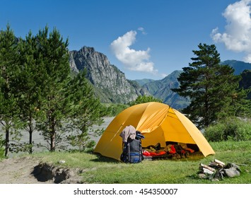 The camping tent and backpack near mountain river in the summer.