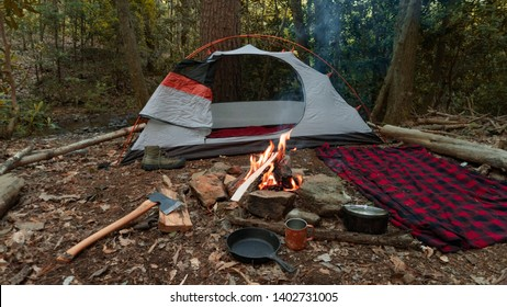 Camping tent in the Blue Ridge Mountains in Asheville, North Carolina. Outdoor lifestyle with axe, cast iron skillet, flannel blanket. Rustic Bushcraft Campsite. Survival shelter in the wilderness.