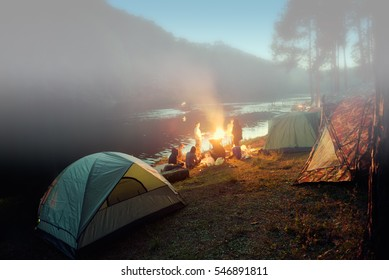 Camping tent with blured image group of backpackers relaxing near campfire, tourist background.