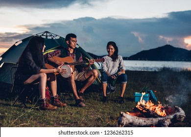 Camping tent camp in nature happy friends group night party bonfire and playing guitar together in summer at nature forest