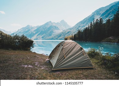 Camping tent in campground at national park. Tourists camped in the woods on the shore of the lake on the hillside. View of tent on meadow in forest. Camping background