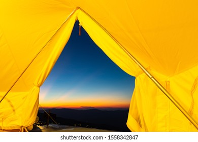 A camping tent glows under crepuscular rays after sunset to a night sky Outdoor Camping adventure