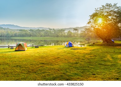 Camping and tent near lake in sunrise