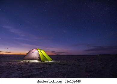 Camping tent at night against amazing sky full of stars, Salar de Uyuni, Bolivia