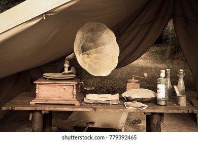 Camping tent with an old record player and various objects on a rustic wooden table.