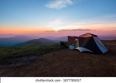 camping tent on the lawn, which is on a high mountain with a view of the mountain complex And dense white fog Reflected in the sunlight in the morning, to tourist and travel concept.