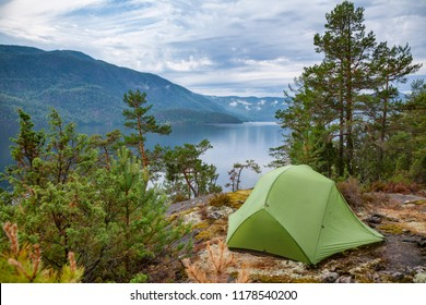 Camping tent at scenic wild campsite on a lake shore with mountain range in background - camping in Norway