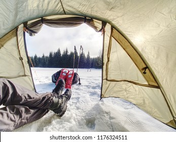 Camping in tent in winter forest. Snowshoes trek in mountains, setting a tent in snow.