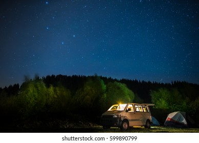 Camping with tents and car under the stars
