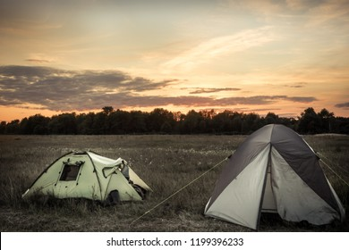 Camping tents on camping sites on summer flatland field plain and dramatic sunset sky during camping holidays