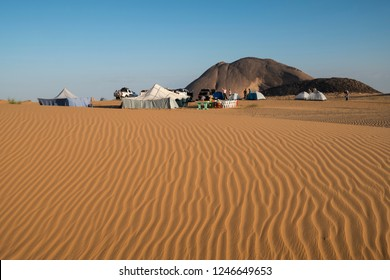 Camping with tents in the Sahara desert with amazing sand dune in foreground