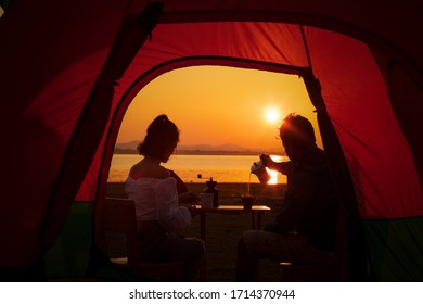 Camping tent,Sunrise inside a Tent,Tourists pour coffee from Mocha Pot, a beautiful sunrise,Romantic lovers