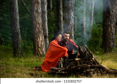 camping, travel, tourism, hike and people concept - happy couple sitting and warming near campfire at camp in forest