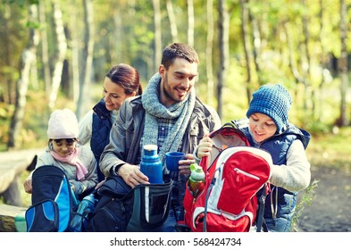 camping, travel, tourism, hike and people concept - happy family with backpacks and thermos at camp