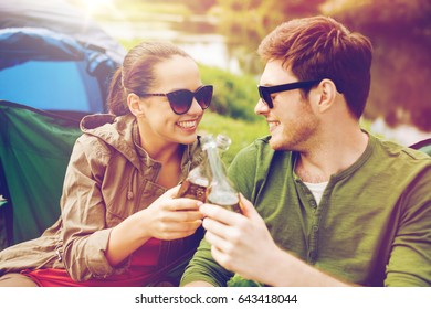 camping, travel, tourism, hike and people concept - happy friends clinking glass bottles and drinking cider or beer at campsite