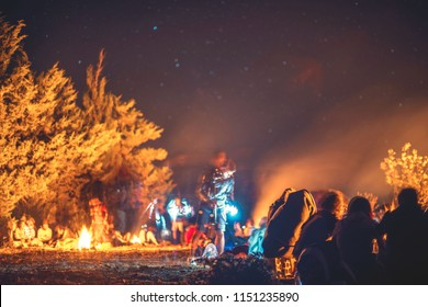 camping under the stars of the night and milky way gathering around a fire