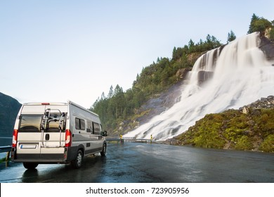 Camping van at beautiful huge waterfall. Amazing cataract at road. Norway.