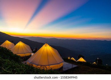 Camping and white tent on the hill with crepuscular rays after sunset background, Chiangrai Thailand
