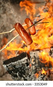 camping in the wild - two smoked barbecue sausages on sticks held over the campfire