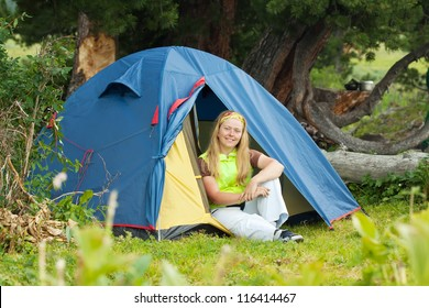 Camping woman resting in front of  tent on the nature