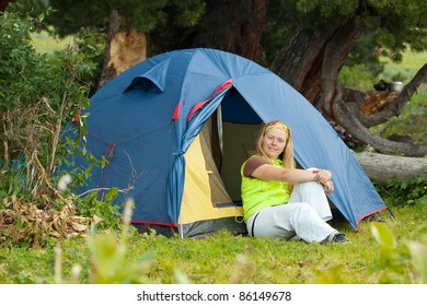 Camping woman resting in front of  tent on  nature