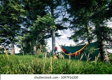 Camping in woods with hammock and sleeping bag on mountain biking adventure trip in green mountains. Travel campsite when mtb cycling with backpack. Bikepacking shelter in wilderness forest, Poland.