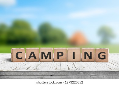 Camping word on a wooden cube sign with a blurry background of a campsite in the summer