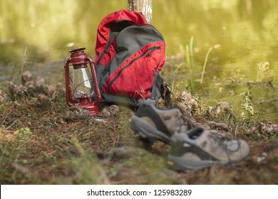 Camping/hiking gear by the side of a placid lake. Shoes,backpack, and lantern.