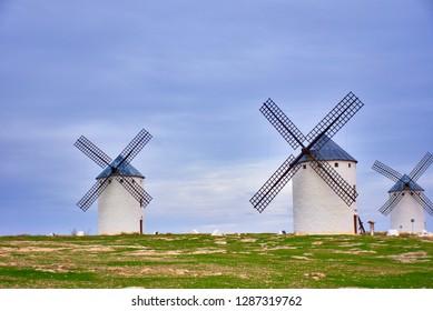 CAMPO DE CRIPTANA, SPAIN - NOVEMBER 22, 2018: Windmills of the route of Don Quixote, Castilla La Mancha, Spain. Sunset on a cloudy day
