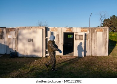 Campo de Mayo, Buenos Aires, Argentina. August 7, 2014. A Blue Helmets trainer walks in front of UN containers during a hostile environment training for journalists.