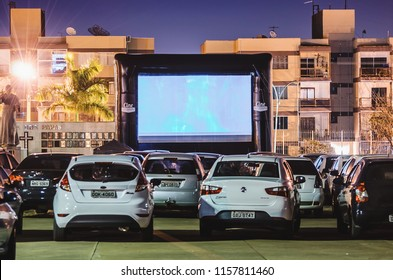 Campo Grande, Brazil - August 16, 2018: Parked cars at Praca do Papa square to watch movies inside the car. Cine Autorama event, drive-in, open air cinema, open to public. Photo at night.