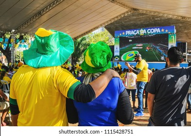Campo Grande, Brazil - June 17, 2018: Couple wearing green and yellow watching a match of the world cup (Brazil vs Switzerland match) at Praça do Rádio Clube square. Outdoors, free event.