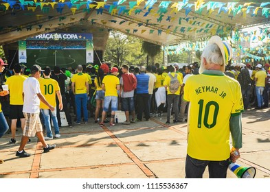 Campo Grande, Brazil - June 17, 2018: old man wearing the Brasil team t-shirt (neymar jr) and watching a match of the world cup at Praça do Rádio Clube square. Outdoors, free event.