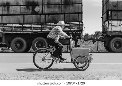 Campo Grande, Brazil - May 24, 2018: Old man riding a old bicycle selling ice creams on a highway to make some money.