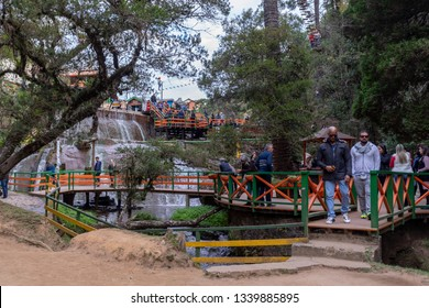 Campos do Jordão, Brazil - June 23, 2018: Tourists at the open air adventure and natural waterfall attraction Silver Fall ('Ducha de prata') in the mountains of Campos do Jordão ('Jordan Fields')