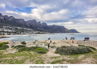 CAMPS BAY, SOUTH AFRICA - JULY 16, 2018: Tourists enjoy the beautiful nature of Camps Bay (Kampsbaai). Camps Bay bordered by spectacular Twelve Apostles Mountain and glittering Atlantic Ocean.