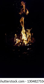 camp-side fire reaching upwards with flames and throwing out sparks