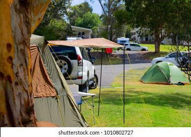 Campsite with eucalyptus trees, cars, caravans and traveller's tents on grass in Australia. Australian campground during a holiday season in Katoomba, Blue Mountains