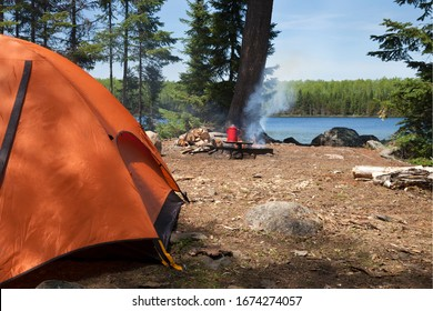 Campsite with orange tent and campfire on a northern Minnesota lake